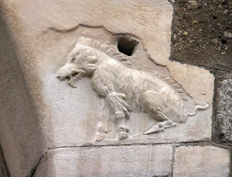 frammento romano incastonato alla base di un voltone della Loggia dei Mercanti