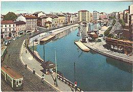 Una cartolina ritrae la Una cartolina ritrae la Darsena nel 1964.conche (Via Conca del Naviglio nella foto di Yorick39)