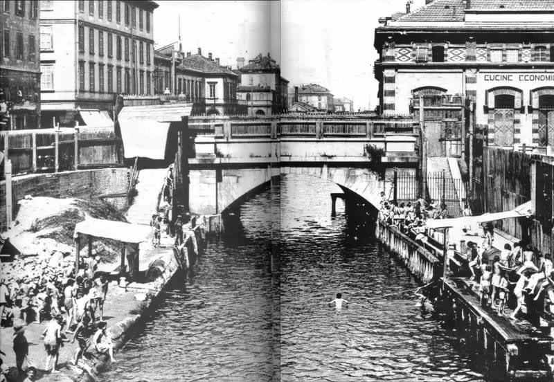 Vecchia foto con i bambini che fanno il bagno all'ingresso della Martesana al Ponte delle Gabelle. Dietro si scorgono le Cucine Economiche, in angolo con l'attuale Via Melchiorre Gioia.