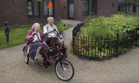 dementia village cc ouple on tricycle