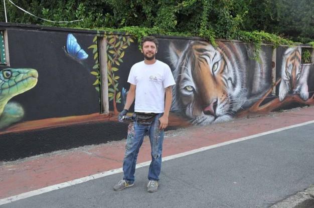 Il murale sulla Via Lessona con Fabio Colombini, in arte Acme (foto il giorno.it)