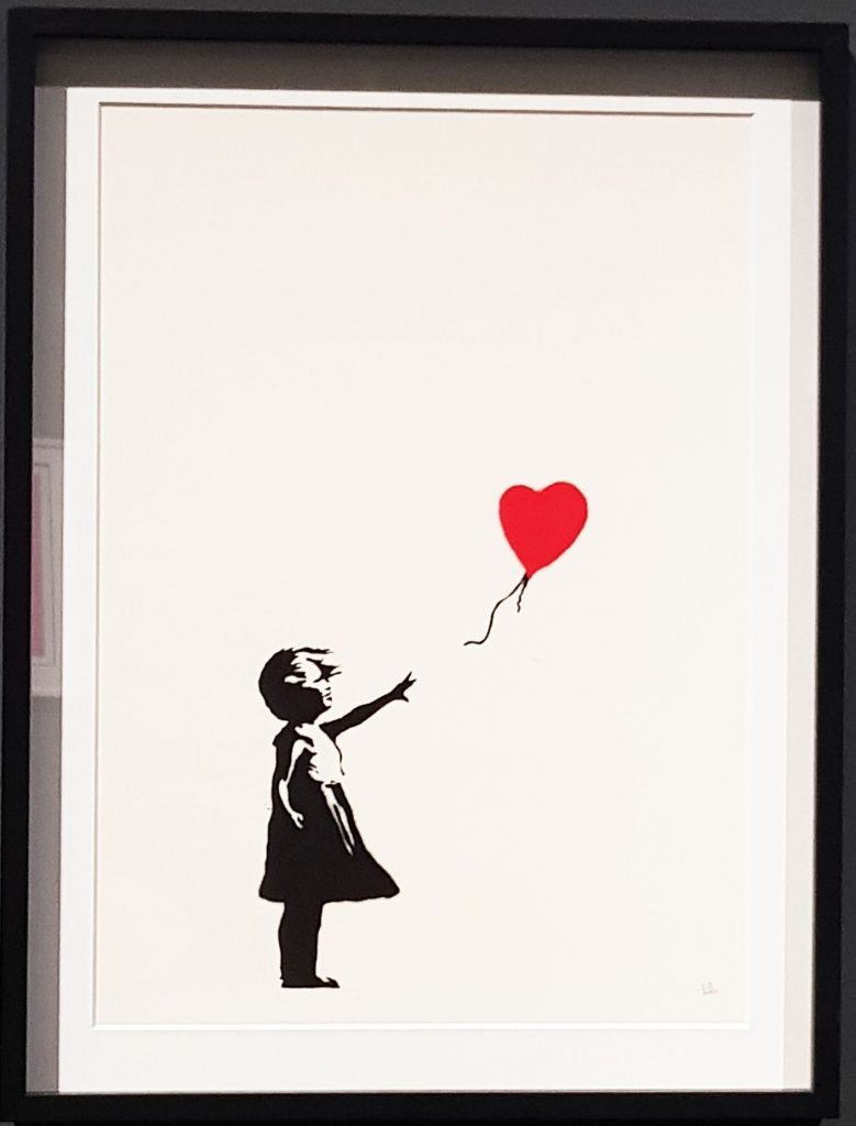 "Immagine contenente l'iconica opera di Banksy ""Girl with red balloon"" del 2004 in mostra al Mudec"